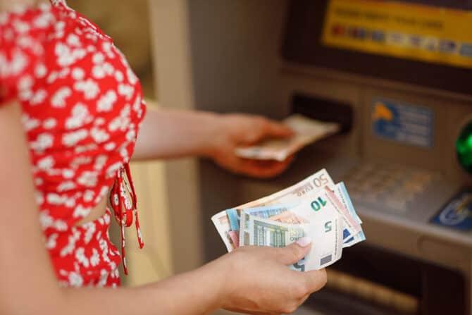 Frau hebt Geld am Automaten ab